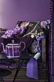 Purple teapot on side table in front of antique bench with purple tassel and scatter cushion