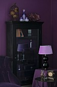 Table lamp with lilac lampshade in front of antique, glass-fronted cabinet against aubergine wall