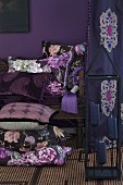 Stack of cushions with different covers on floor and on antique bench against purple wall