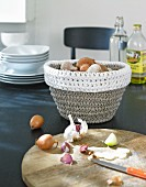 A crocheted onion basket with a wooden chopping board in the foreground