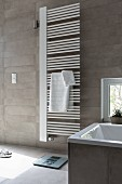 A white hand towel heater on a grey-tiled wall in a modern bathroom