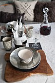 Place setting with silver bowl on rustic wooden board and carafe of red wine
