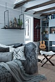 Scatter cushions and animal-skin blanket on sofa in wood-clad cabin interior