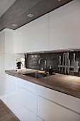 Modern industrial-style kitchen with white glossy fronts and wooden worksurface