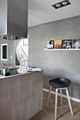 Island counter and bar stool in modern kitchen with concrete-effect walls