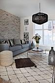 Skandinavisches Wohnzimmer mit Backsteinwand und orientalischen Accessoires