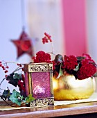 Tealight in miniature lantern and flower arrangement in gilt vase