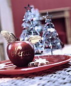 Apple, festively decorated with angel's wings as Christmas place tag