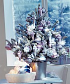Small Christmas tree lavishly decorated with baubles & artificial snow