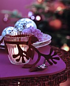 Glass tealight holder with felt decoration on table