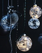 An Bändern aufgehängte Weihnachtskugeln in Schwarz & aus Glas