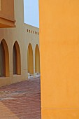 Arched windows and doorways and yellow walls in Oriental courtyard