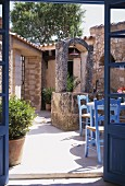 View through open terrace doors into sunny, Mediterranean-style courtyard with blue-painted chairs