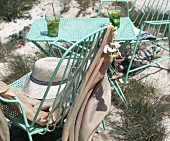 Refreshing drinks, turquoise-painted, metal table with matching chairs and sun hat on beach
