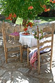 Mediterranean-style set table and wooden chairs on terrace