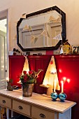 Wooden Christmas trees on console table against red wainscoting