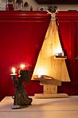Wooden Christmas tree decorated with tealights and angel figurine holding candle in front of red wainscoting