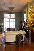 Christmas tree lit with fairy lights, stucco ceiling and Chesterfield sofa in living room