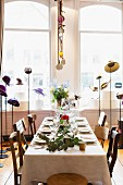 Set table surrounded by various hats on hat stands
