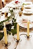 Filigraner Kerzenhalter aus Metall mit Blütenmotiv auf gedecktem Tisch