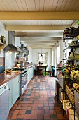 Terracotta floor tiles and dining area in elongated kitchen