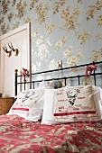 Scatter cushions printed with festive reindeer motifs on metal bed