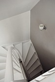 View down purist stairwell with pale grey walls & white, winding staircase
