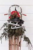Vintage sledge decorated with ice skates, conifer branches and pine cones