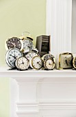 Collection of various old alarm clocks on mantelpiece