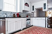 Traditional, red and white patterned rug in modern country-house kitchen with poinsettia in red pot