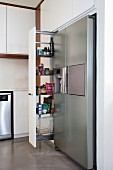 Open, sliding shelves next to stainless steel fridge-freezer in modern kitchen