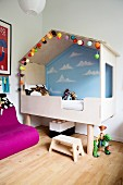 Modern cubby bed with painted wall and fairy lights in child's bedroom with Scandinavian ambiance