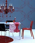 Red chandelier above table with patterned runners in front of blue wall with ornate pattern