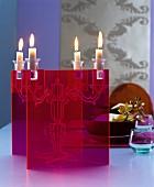 Transparenter roter Kerzenständer mit brennenden Kerzen als Tischdekoration