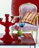 Pastel, Baroque armchair with yellow-striped cushion against red background and brightly coloured glasses on red table