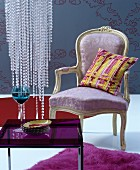 Pastel, Baroque armchair with yellow, striped cushion against blue-grey background with ornate pattern and bead decoration above purple glass table