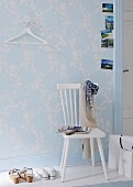 A white kitchen chair against a wall with pastel-blue and white floral-patterned wallpaper