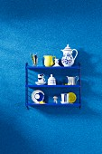Crockery on a blue shelf on a wall with a blue faux uni patterned wallpaper