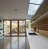 White worksurface in designer kitchen with exposed brickwork and view of terrace, steps and garden wall through terrace windows