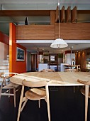 View across dining table to wood-clad gallery and orange partition wall