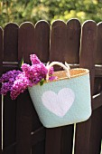 Lilac flowers in shopping basket hanging on wooden garden fence