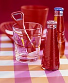 Small bottle of Campari and glass holding cocktail sticks and red bottle opener on pink, checked surface