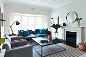 Elegant coffee table on striped rug and armchair and sofa in various shades of grey in traditional living room