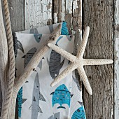 Dried starfish, driftwood & napkin with maritime print on weathered wooden surface
