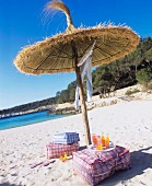 Floor cushions & drinks under straw parasol on sandy beach
