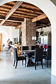 Rustic wood-beamed ceiling and pillars in open-plan, renovated, Italian country house