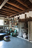 Reading corner in historical interior with rustic wood-beamed ceiling and modern concrete floor