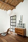 Renoviertes Dachgeschosszimmer mit Antikkommode und gerahmten modernen Skulpturen und Tierobjekt