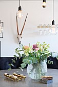 Spherical glass vase of flowers and tealights in brass candleholder on table below bulb-style pendant lamps
