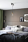 Comfortable double bed in modern bedroom with grey-painted wall